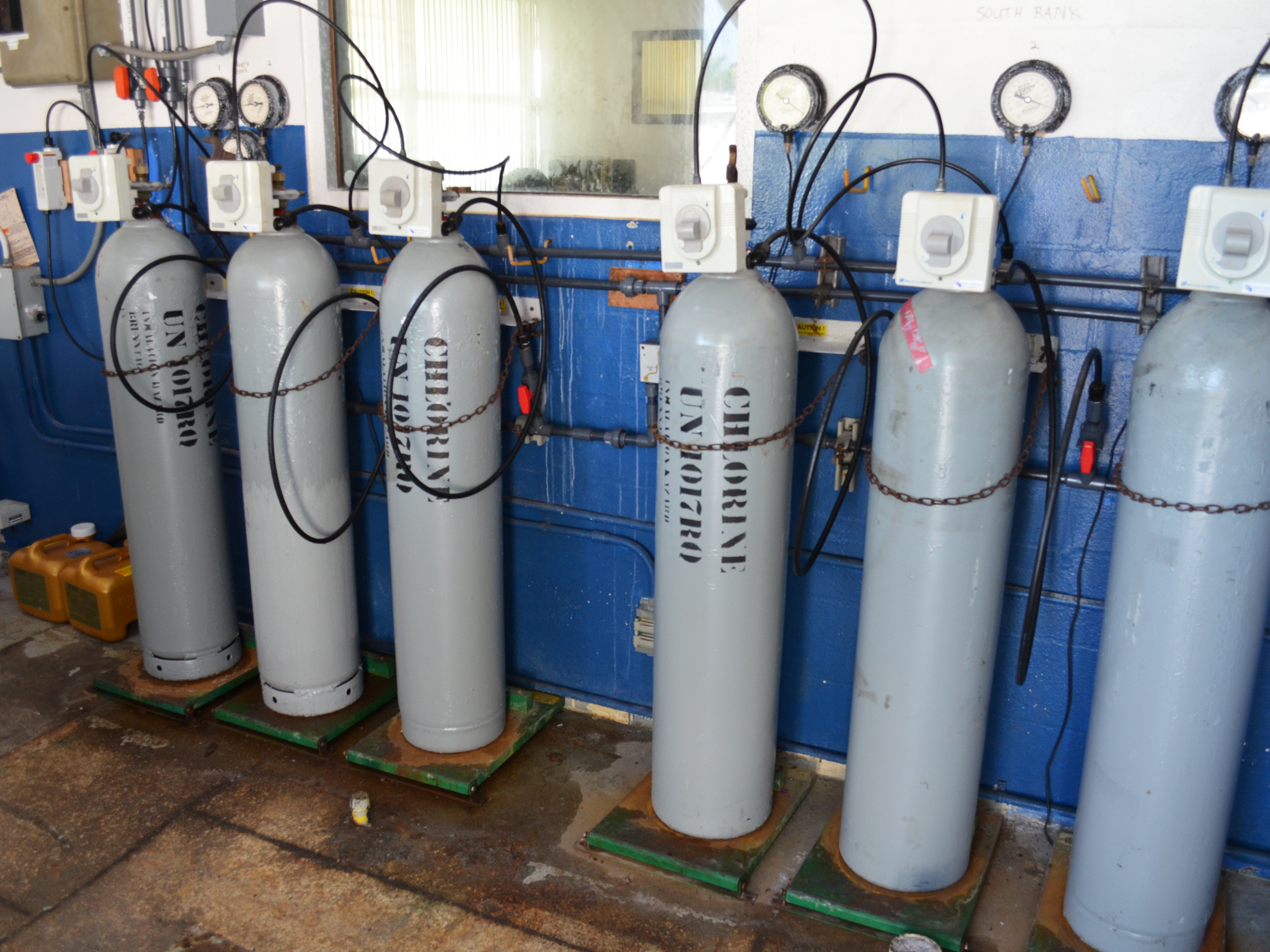 Three silver-colored canisters of chlorine hooked up to the water supply in the water plant.